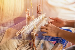Wheel Spinning Yarn with Yellow Thread to work for Weaving machine and Thai traditional Silk. Artists artisans handicrafts handmade manufacturing motton silk hand loom Thai.
