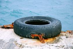 Wheel tire rescue ring. Rusty chains and pipes on the old marina. Black sea landscape, Crimean peninsula in the winter. Sea berth. Travel photos. Autonomous Republic of Crimea.
