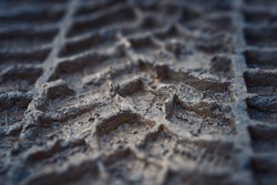 Wheel track on mud closeup. Tyre track on dirt, messy ground. Off road drive on dirty ground, bad road conditions. Car track on the ground. Imprint tires on wet clay. Dirt with traces from the wheel