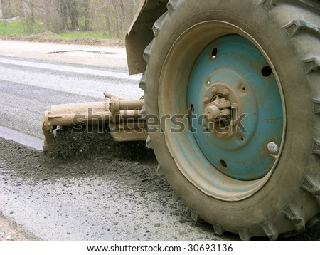 Wheel tractor cleaning asphalt road by brush before asphalt laying