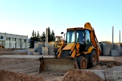 Wheel tractor excavator loader with bucket at construction works in industrial site or sandpit quarry. Worksite outdoors, heavy equipment machinery for heavy industry.