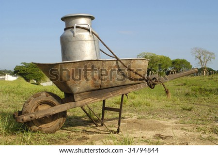 Wheelbarrow and milk churn at a farm at Cuba