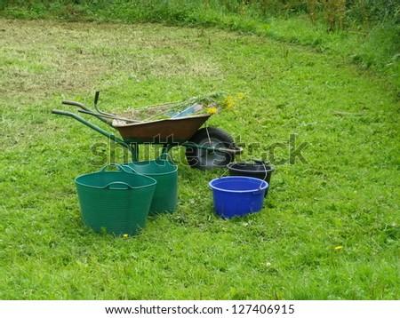 wheelbarrow and trugs with buckets in a garden