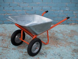 Wheelbarrow for garden construction on two wheels against background of brick wall