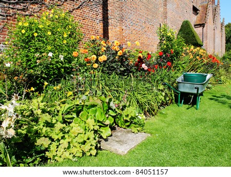 Wheelbarrow parked next to a colorful border of Summer Flowers in an English walled garden
