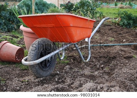 Wheelbarrow sitting in a vegetable garden