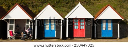 Wheelchair and colourful beach huts with blue and red doors in a row traditional English structure and shelter found at the seaside panorama
