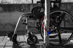 Wheelchair attached to a tree with an anti-theft lock. You won't need it anymore! Let it stand here.
