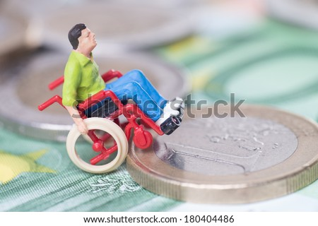 Wheelchair user with euro coins and euro banknote / Wheelchair user