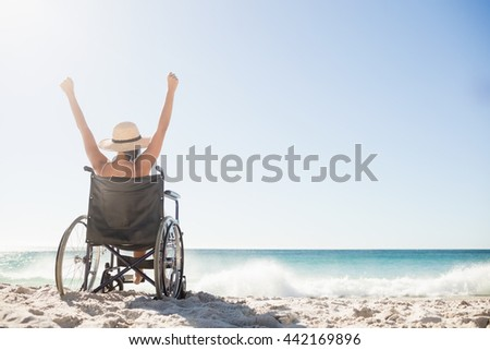 Wheelchair woman sitting with arms up on the beach Stock photo ©