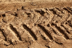 Wheeled tractor footprint . Tractor tire track imprinted into dirt
