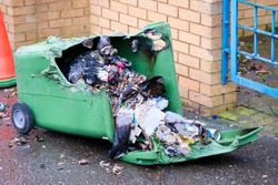 Wheelie bin vandalism on side burnt out by fire by vandals in council estate London arson attack