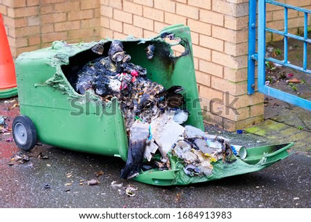 Wheelie bin vandalism on side burnt out by fire by vandals in council estate London arson attack Stock photo ©