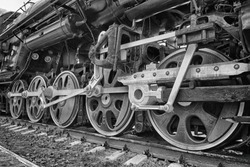 wheels of an ancient locomotive close-up, retro vehicle, black and white photo