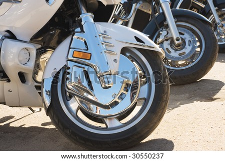 Wheels of several motor bikes - stock photo