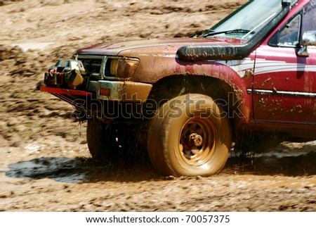 Wheels spinning on an off road vehicle as it skids across the mud