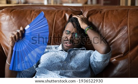 When ac is broken. Overheated millennial afro american man recline on couch at home get heat stroke use hand fan. Sweaty black guy hipster tired of breathing hot air need to buy repair air conditioner ストックフォト ©