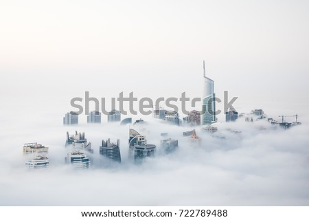 When cold desert air meets warm ocean air at the start of the winter, Dubai witnesses a unique sight of world's highest skyscrapers drowning in fog. Dubai, UAE. #722789488