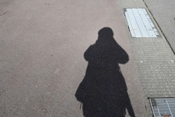 When looking down at the shadow of a woman on a concrete road, the shadow has long legs, a short body and is beside the drain. The sunlight that shines through the body creates shadows. That looks fun