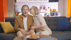 When the blond old woman whispers disgraceful or funny things in the ear of her bearded old husband, she and her wife laugh in laughter. The concept of whispering in the ear, saying shameful things,