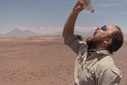 When the desert ties up your throat. The last drop of water in the desert has a bitterweet taste. Male with sunglasses drinking the last waterdrop of the bottle in the driest desert on earth: Atacama