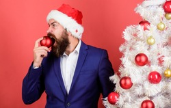 Where are my cookies. Need for eat. Appetite and hunger. Feeling hungry. Santa bearded man biting red christmas ball. Hungry guest. Restaurant concept. Lunch dinner menu. Inedible food. Hungry Santa.
