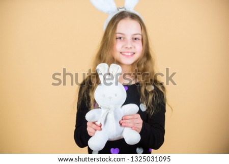 Where did Easter rabbit come from. Little girl holding Easter rabbit toy. Happy child playing with Easter bunny rabbit. Small kid getting white rabbit gift on Easter day.