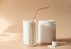whey drink in a high glass. whey protein vanilla cocktail. a jar with protein powder and a scoop of powder on a table. morning drink for health and beauty.