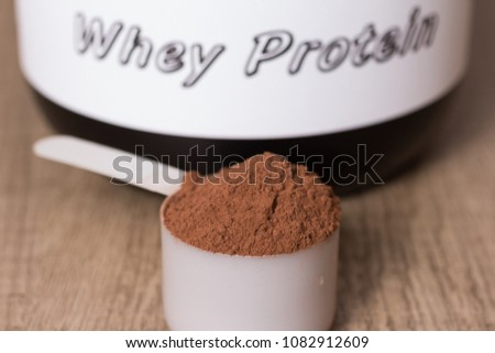 Whey protein food supplement for training and exercise. White scoop with chocolate flavour powder and black jar. Wooden table. Close up, texture
