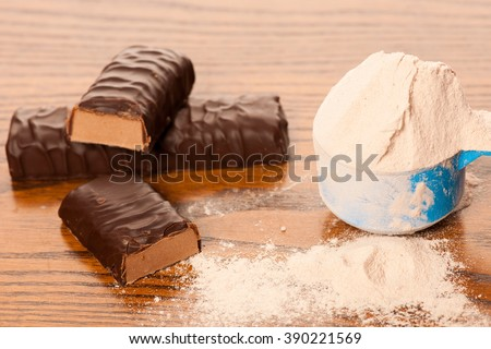 Whey protein powder in measuring scoop and chocolate protein bar on wooden background.