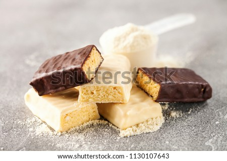 Whey protein powder in measuring scoop and different energy protein bar on black background.