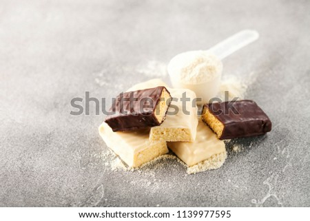 Whey protein powder in measuring scoop and energy protein bar on black background.