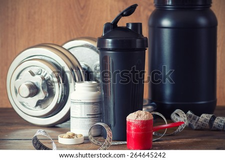 Whey protein powder in scoop with vitamins and plastic shaker on wooden background. Selective focus, shallow DOF