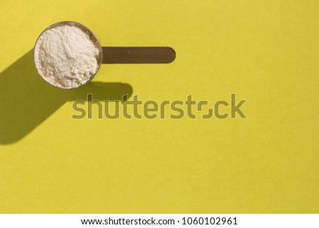 Whey protein powder sports bodybuilding supplement. Minimal concept and hard light. Scoop with vanilla flavoured powder on yellow background.
