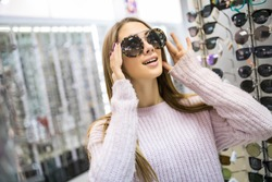 Which one is better fit me. Portrait of cheerful hesitating woman in optician store, making decision, holding stylish sunglasses, choosing what she should buy. Great discounts for buying two pairs