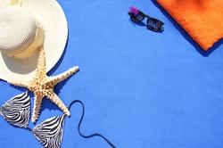 Whicker hat, bikini, sunglasses, towel and seashell on the blue background