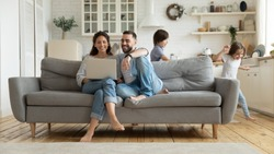 While funny active daughter and son running parents sit on sofa resting using pc online services plan family holiday choose tour booking online apartments, e-commerce usage on weekend at home concept