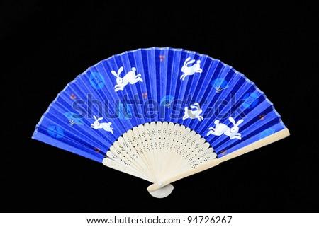 Whimsical blue folding fan with white rabbits from Japan isolated on black velvet background