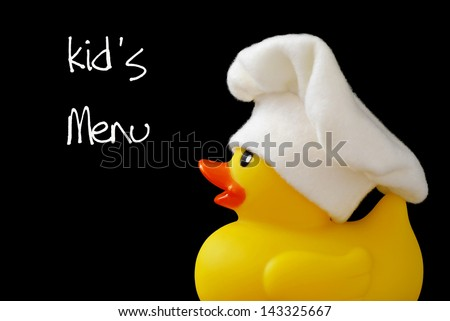 Whimsical cooking concept of little rubber ducky wearing a chef's hat (made of fleece fabric).  Macro on black background with text.