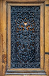 Whimsical ornate gratings of vintage wooden door with framed door panel. Closeup of antique ornate metal lattice with backlight. Antique door in Paris France. Baroque architecture details.