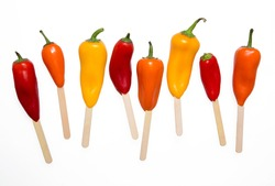 Whimsical, playful image of vibrant, colorful peppers on wooden sticks