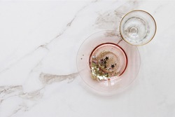 Whimsical simple party place setting with pink and gold vintage glass with star confetti. Copy space on white marble.