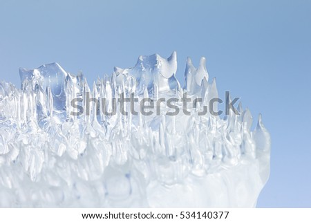 Whimsical surface ice closeup on blue sky background. Copy space. Texture. #534140377