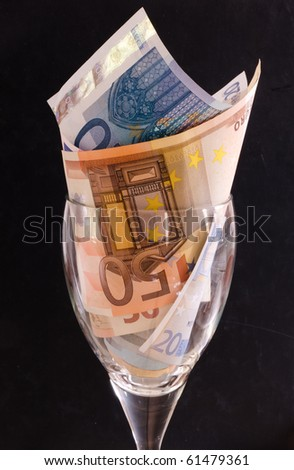 Whine glass filled with Euro banknotes