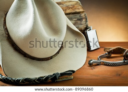 whip,spurs and hat, on wood