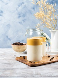 Whipped dalgona coffee drink in glass mug on wooden board. Cozy breakfast with trendy beverage