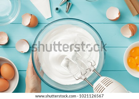 Whipped egg whites cream to perfect peaks in glass bowl with mixer and hand on blue wooden table. Step by step recipe of meringue cookies top view.