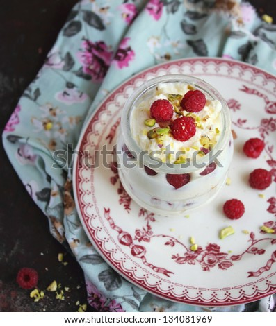 Whipped ice cream dessert with white chocolate, fresh raspberry and chopped pistachios in a jar