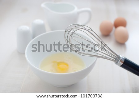 Whisk and eggs in white bowl