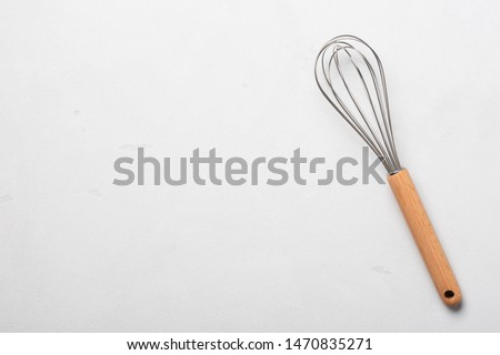 Whisk cooking egg beater mixer whisker new clean with wooden handle on stucco table top view